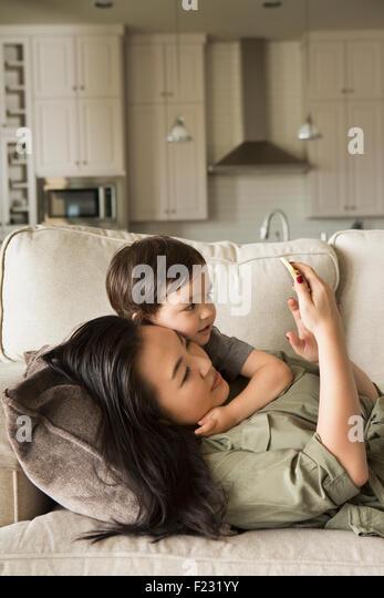 Frau liegt auf dem Sofa kuscheln mit ihrem kleinen Sohn und mit Blick auf ein Handy. Stockbild