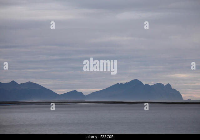 Bergen an der Küste im Hof in Südost-Island. Nordatlantik liegt hinter einer dünnen Halbinsel des Stockbild