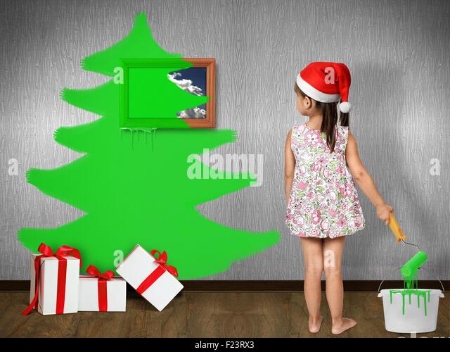 Lustige Kinder gekleidet Weihnachtsmütze, zieht Weihnachtsbaum an Wand zu Hause Xmas-Konzept Stockbild