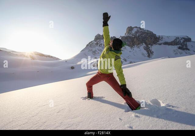 Mann tut Yoga auf schneebedeckten Berg bei Sonnenaufgang, Tirol, Österreich Stockbild