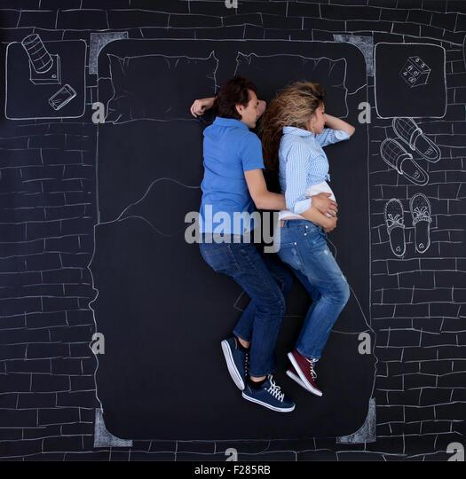 Junges Paar im Bett schlafen, umarmt Hand in Hand, der Mann seiner Frau. Junger Vater mit einer Hand auf Mamas Bauch Stockbild