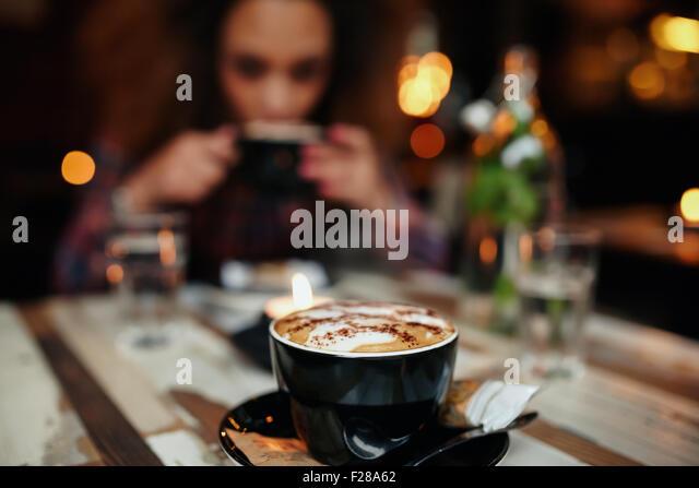 Nahaufnahme Schuss Tasse Kaffee am Tisch im Café, mit einer Frau Kaffeetrinken im Hintergrund. Tasse Kaffee Stockbild