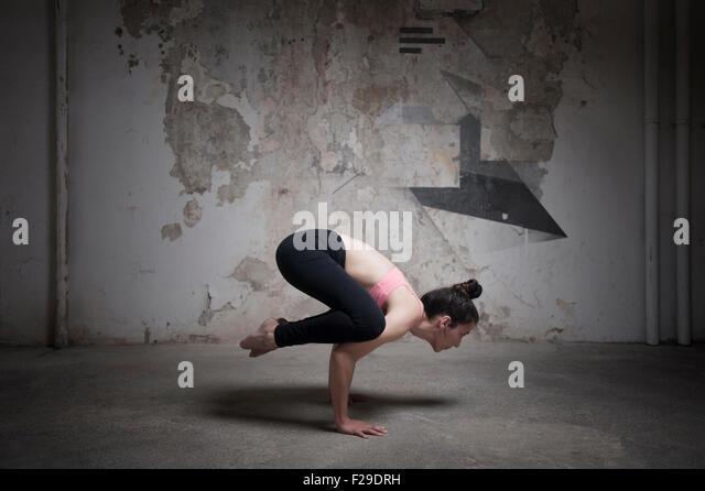 Mitte Erwachsene Frau üben Bakasana im Yoga-Studio, München, Bayern, Deutschland Stockbild
