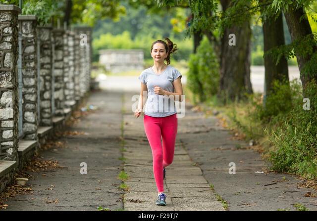 Ausgeführt. Junge Frau im Park joggen. Morgens joggen. Gesunde Lebensweise. Stockbild