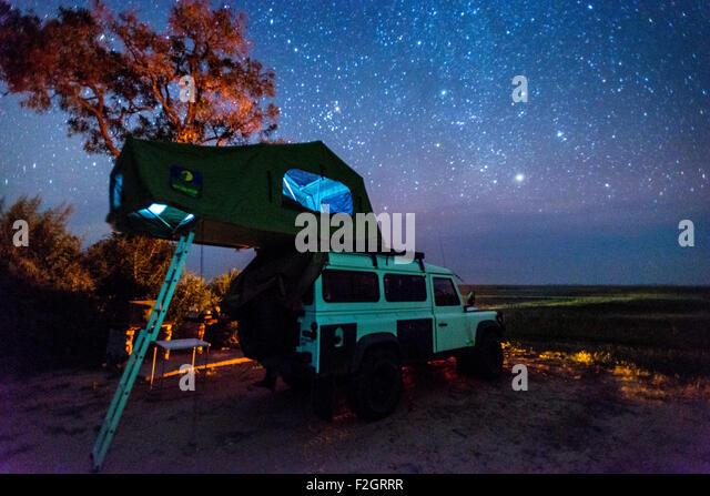 Land Rover geparkt mit einem Pop-up-Zelt auf dem Dach unter dem Nachthimmel in Botswana, Afrika Stockbild