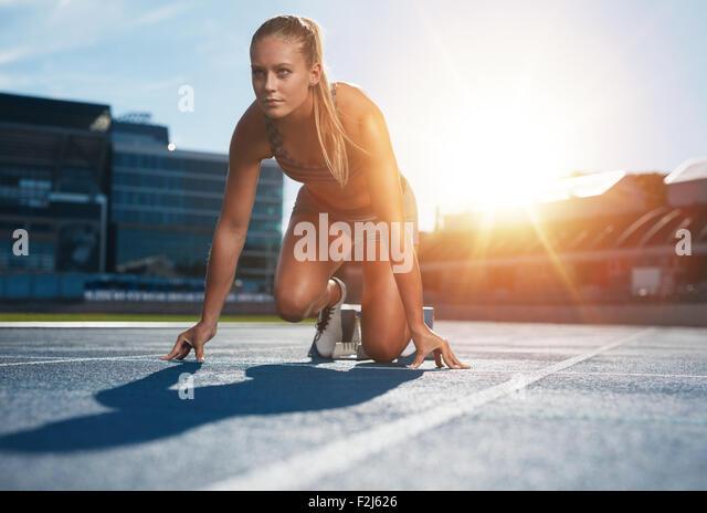 Fit und selbstbewusste Frau in Startposition für den Betrieb bereit. Weibliche Athleten kurz vor dem start Stockbild