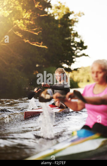Zwei Frauen Rennen in Kajaks an einem See Stockbild