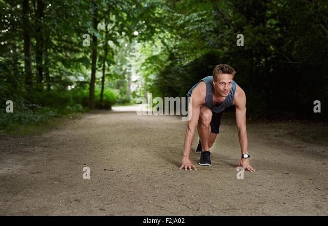 Schönen athletischen Mann in Stellung Start und schauen in die Ferne im Park Stockbild