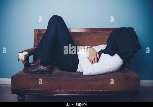 Junger Geschäftsmann auf Sofa schlafen Stockbild