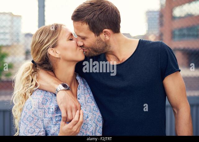 Amorous attraktive junge Paar einen romantischen Kuss genießen, wie Sie Arm in Arm im Freien in einem städtischen Stockbild