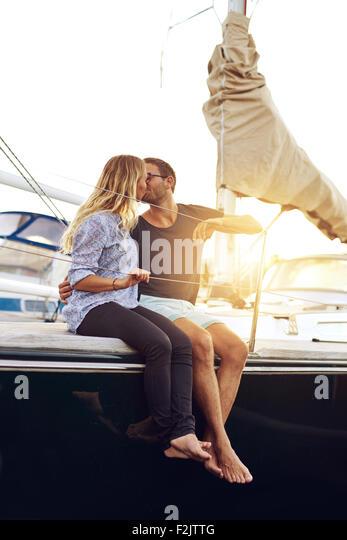 Süße junge Paar küssen auf dem Deck der Yacht bei Sonnenuntergang. - Stock-Bilder