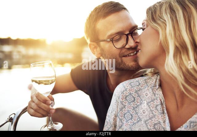 Paar küssen sanft bei einem Glas Wein Stockbild