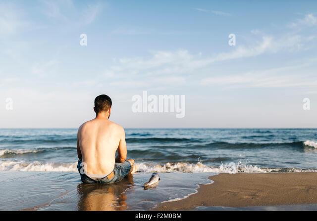 Rückansicht der junge Mann sitzt am Meer neben einem gefangenen Fisch Stockbild