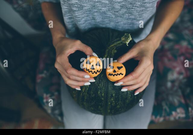 Frau hält einen Keks für Halloween Stockbild