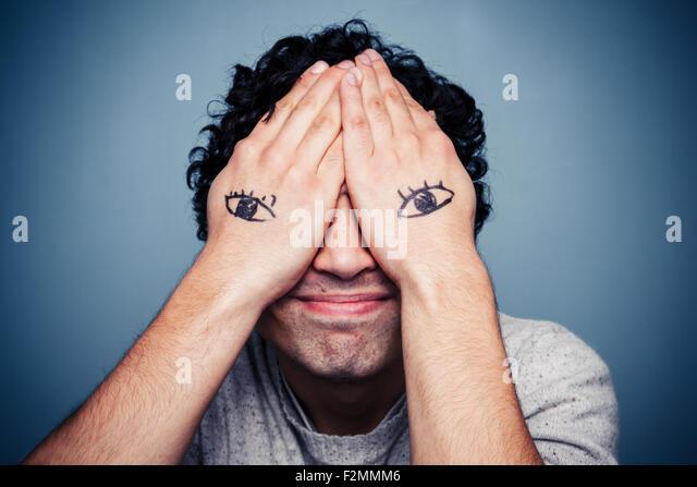 Junger Mann mit Augen auf seinen Händen gemalt Stockbild