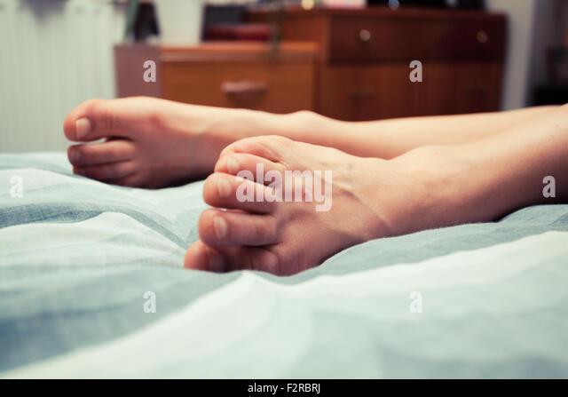 die Füße einer jungen Frau auf die Bettwäsche in häuslicher Umgebung Stockbild