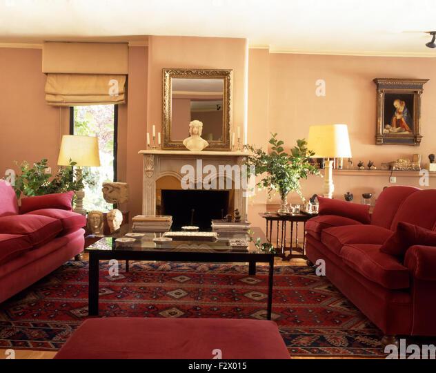 Tief rosa Sofas und Glas gekrönt Kaffee im spanischen Wohnzimmer mit eine orientalische Wolldecke eingereicht Stockbild