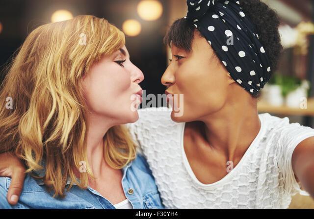 Verspielte necken attraktive junge Frauen Freunde verziehen sich für einen Kuss, wie Sie jede andere Fläche Stockbild