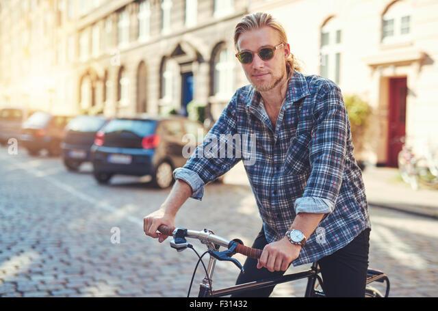 Junger Mann auf seinem Fahrrad in der Stadt, die immer bereit zu reiten Stockbild