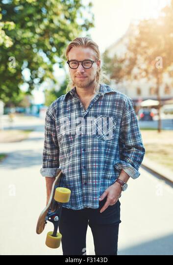 Porträt von cool junger Mann mit langen Haaren und Brille tragen eine skateboard Stockbild