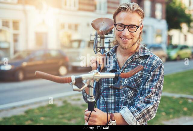 Young Man City Lifestyle. Fahrrad auf der Schulter tragen. Lächelnde Porträt Stockbild