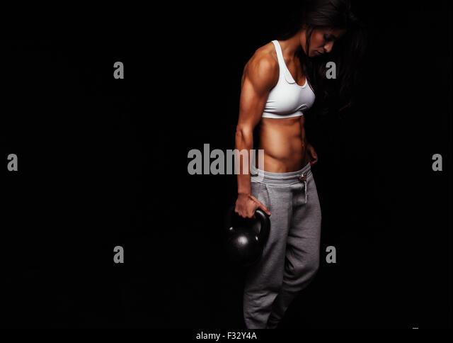 Muskulöse Frau Crossfit Übung zu tun. Harten Fitness weibliches Modell mit Wasserkocher Glocke auf schwarzem Stockbild