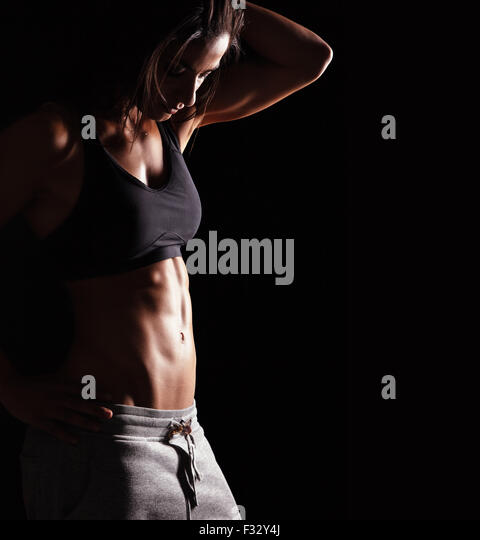 Bild von Fitness-Frau in Sportkleidung auf der Suche nach unten. Junge weibliche Modell mit muskulösen Körper. Stockbild