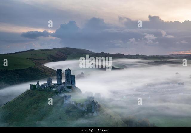 Corfe Castle im Nebel bei Sonnenaufgang, Dorset, England Stockbild