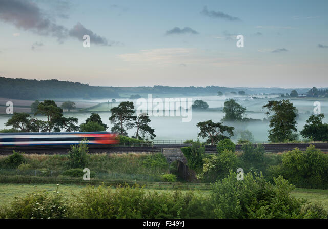 London Waterloo in Exeter Zug vorbei Milborne Docht auf einen nebligen Sommer Morgen, Somerset, England, UK Stockbild