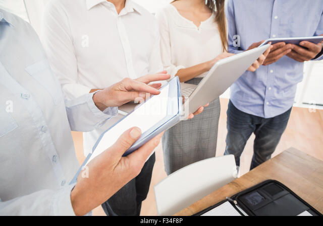 Geschäftsleute, die Verwendung mehrerer elektronischer Geräte Stockbild