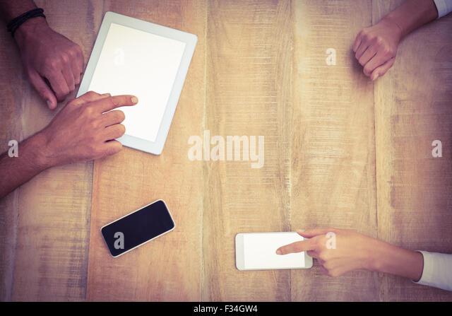 Lässige Geschäftskollegen mit mehreren Geräten Stockbild