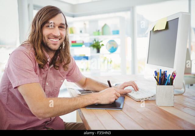 Glücklich Hipster auf Grafiktablett und Computer arbeiten Stockbild