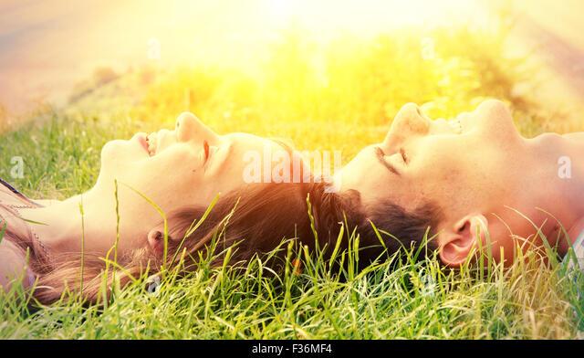 Junge glückliche Paar in der Sonne liegen Stockbild