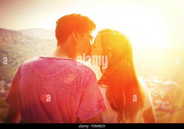 Jung, paar in der Sonne küssen Stockbild