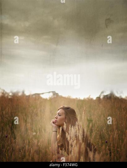 Mädchen sitzen zwischen Feldern mit einem stürmischen Himmel Stockbild