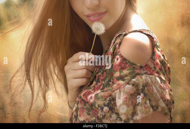 halbes Gesicht von einer Frau rosa Lippen Löwenzahn blondem Haar Stockbild