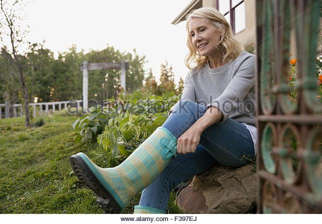 Frau auf karierten Gummistiefel im Garten Stockbild