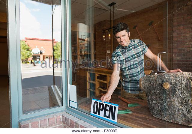 """Porträt-Arbeiter drehen Schild """"geöffnet"""" im Schaufenster Stockbild"""