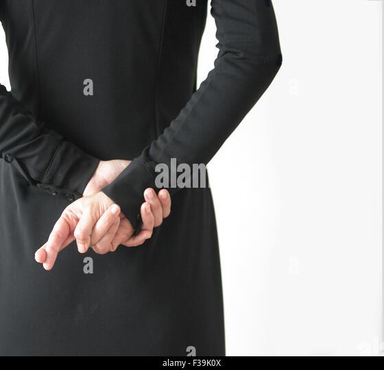 Rückansicht einer Frau mit Fingern hinter Rücken gekreuzt Stockbild