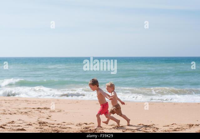 Zwei jungen, die entlang des Strandes Stockbild