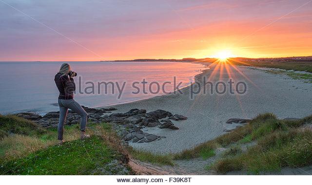 Frau, die ein Foto eines Sonnenuntergangs, Brusand, Rogalund, Norwegen Stockbild