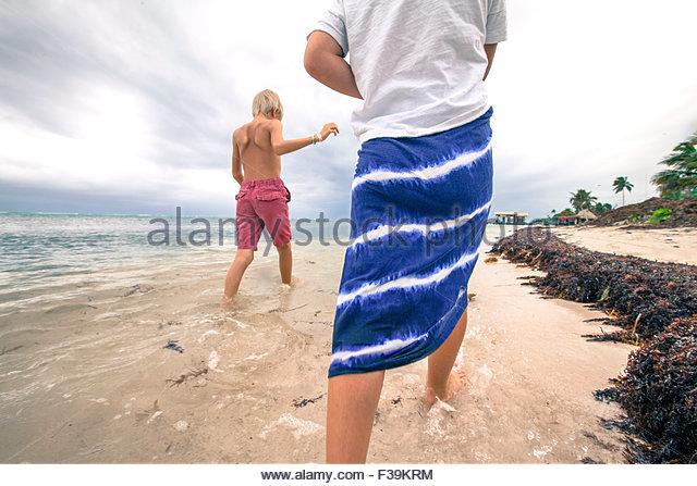 Zwei Kinder, die zu Fuß in das seichte Wasser am Strand, Belize Stockbild