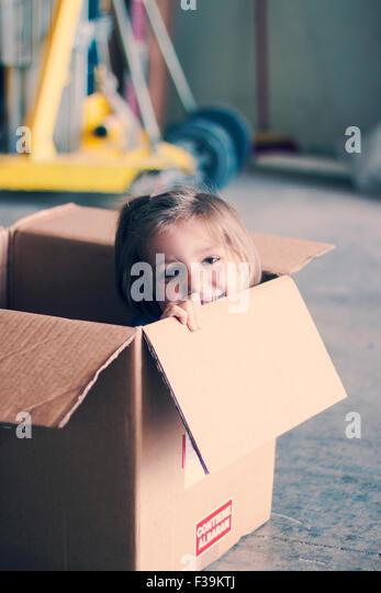 Lächelndes Mädchen sitzen in einem Karton Stockbild