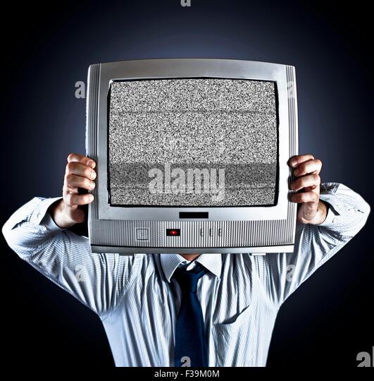 Mann, der alte altmodischen Fernsehen vor sein Gesicht hält Stockbild