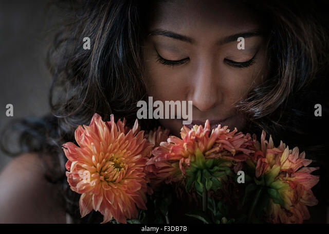 Junge Frau, die Blumen riechen Stockbild