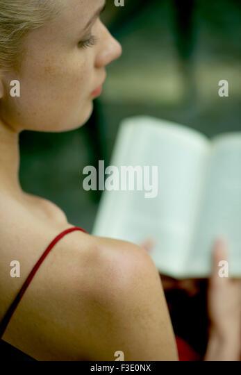 Junge Frau Buch zu lesen, über die Schulter-Blick Stockbild