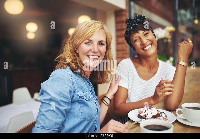 Zwei attraktive junge multiethnischen Freundinnen genießen Sie Kaffee und Kuchen zusammen in einer Cafeteria Stockbild