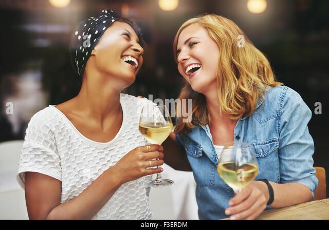 Zwei junge attraktive vivacious multiethnischen weibliche Freunde feiern und zusammen lachen über einem Glas Stockbild