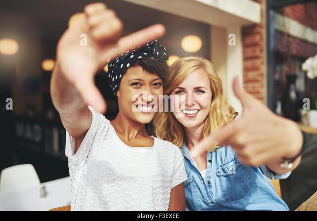 Spaß junge Damen framing ihre Gesichter mit Ihren Fingern in einer kreativen Selbstportrait als Sie sitzen Stockbild