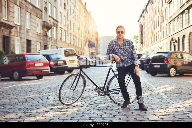 Wohnen in der Stadt, Porträt des jungen Mann auf seinem Motorrad sitzen Stockbild